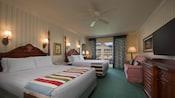 Deux grands lits avec tête de lit, un téléviseur, une commode, un canapé-lit et un balcon