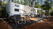 Campsite with an RV parked on its concrete pad that includes a charcoal barbecue grill and picnic table