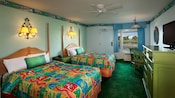2 double beds with bright tropical-colored bedding opposite a green media cabinet with flat-screen TV