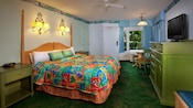 King bed with bright tropical-colored bedding opposite a green media cabinet with flat-screen TV