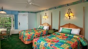 2 double beds with bright tropical-colored bedding and green carpeting
