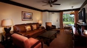 A brown-and rust-colored living room with a leather sofa, dark wood coffee table and 2 cushioned side chairs