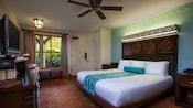 Un très grand lit en face d'une commode de télévision, un bureau et derrière, une fenêtre avec vue sur la piscine et une porte
