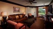 Um sofá, mesa de café, 2 poltronas, Cômoda com TV, mesa redonda e, atrás, uma janela e uma porta da frente