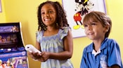 2 children playing a video game with a framed print of Mickey Mouse and Minnie Mouse in the background