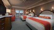 Duas camas queen-size em frente a uma cômoda com uma TV e sofá, ao lado de uma porta de vidro da sacada