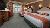 Duas camas queen-size em frente a uma cômoda com um minibar e uma TV embutida