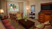 Uma mesa de centro com 2 poltronas, perto de uma mesa de jantar com 4 cadeiras, sofá e uma cômoda com TV