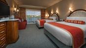 Duas camas queen-size em frente a uma cômoda com uma TV e sofá, ao lado de uma porta de vidro da sacada com cortinas