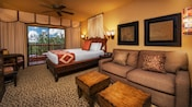 Sofa and coffee tables, wall art and sconces, queen bed with curtained headboard, balcony view
