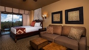 Queen bed with curtained headboard, sleeper sofa, coffee tables, wall art, balcony view