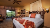 African-themed queen bed with headboard, sofa, coffee table, wall sconces, balcony view