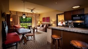 Kitchen counter area, stools, lamps, tables, chairs, sofa, framed art, ceiling fan and patio view