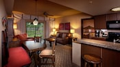Cabinet drawers, art, sofa, chairs, lamps, tables, ceiling fan, patio view and adjoining kitchen area