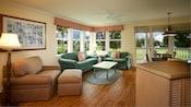 Uma área de estar mobiliada com uma poltrona-cama, ottoman, mesa de café, sofá e sofá-cama queen