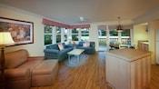 Uma ilha da cozinha virada para a área de estar mobiliada com uma poltrona, ottoman, mesinha de café e 2 sofás