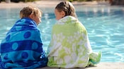 A boy and his older sister, each wrapped in a towel, sit side-by-side with their feet in a pool