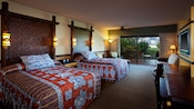 2 queen beds with oversized woven headboards and boldly graphic bedspreads adjacent to patio with lagoon view