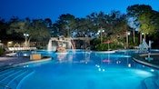 Large swimming pool with softly undulating borders lit up at night with wooden aqueduct water features
