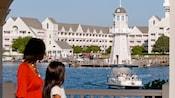 Una mujer y una niña observan el lago frente a Disney's Yacht Club Resort