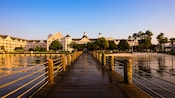 View of a wooden boardwalk leading to Disney's Yacht Club in the distance