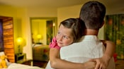 A father carries his happy young daughter into a colorful room at a Disney Resort