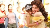 Princess Belle hugs a girl wearing a Disney Princess headband