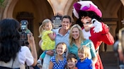 A Disney PhotoPass photographer snaps a picture of a family of six posing with Captain Hook