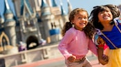 Two young girls smile as they skip hand-in-hand outside Cinderella Castle in Magic Kingdom park