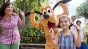 Une petite fille et sa mère imitent Pluto qui tient ses oreilles en tenant leurs cheveux de chaque côté de leur tête pour créer de fausses oreilles tombantes