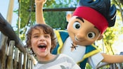 An excited young boy crosses a bridge on A Pirate's Adventure attraction as Captain Jake trails closely behind him