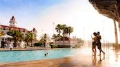 A man and a woman wave at 2 kids swimming in a pool at Disney's Grand Floridian Resort & Spa