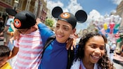 4 smiling siblings including a young boy, a tween girl and 2 tween boys walk shoulder to shoulder through Main Street USA