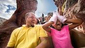 Une petite fille se couvre les yeux avec les mains vêtues de gants de Mickey tout en dévalant Splash Mountain avec son père