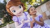 3jeunes filles vêtues de costumes de princesse inspirés de La Reine des neiges rencontrent Anna et Elsa en face du château de Cendrillon