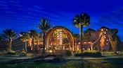 L'extérieur illuminé la nuit du Disney's Animal Kingdom Lodge avec une girafe et 2zèbres qui se promènent sur le terrain