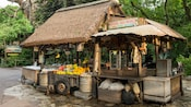 A rustic kiosk called Harambe Fruit Market displaying fresh fruit, bags of chips and assorted snacks