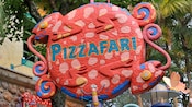 An outdoor iguana-themed sign for Pizzafari welcomes Guests at Disney's Animal Kingdom theme park