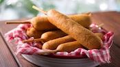 A plate of classic corn dogs made from battered and fried hot dog links