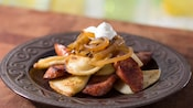 Pierogi piled high and tossed with kielbasa with a topping of caramelized onions and sour cream