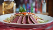 Ahi tuna slices on a plate with cabbage, radishes, carrots, cucumber, fennel, and wonton chips