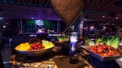 Bowl of fruit and 2 bowls of salads next to pillar candle on table in front of House of Blues stage