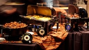 Tables, draped with table clothes, hold 4 buffet warmers with potatoes, scrambled eggs, bacon and sausage
