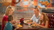 A mother and father smiling while they enjoy a meal at Splitsville alongside their son and daughter