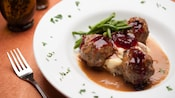 Norwegian meatballs, mashed potatoes and haricots verts with lingonberry sauce, with a fork