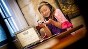 Happy girl wearing princess tiara and holding a crystal slipper, with elegant signed Princess Proclamation