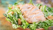 Romaine lettuce topped with slices of roasted chicken, Caesar salad dressing, parmesan and croutons