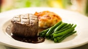 Grilled tenderloin of beef on a plate with green beans and gratin dauphinois potatoes