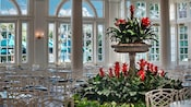 White wrought-iron chairs, tables, arched windows and red bromeliads inside Liberty Inn