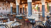 Flickering lamps cast glimmers of light onto the outdoor setting of a Mediterranean-themed eatery